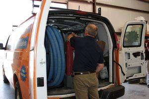 Water Damage Restoration Technician Prepping Van At Warehouse